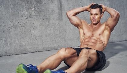 Bauchmuskeln trainieren: Foto von einem Mann beim Bauchtraining auf dem Boden.