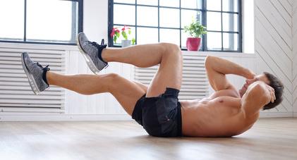 Effektives Bauchtraining: Foto von einem Mann beim Training der seitlichen Bauchmuskeln auf dem Boden mit freiem Oberkörper.