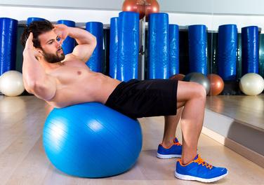Effektives Bauchtraining: Foto von einem Mann beim Training der Bauchmuskeln auf einem Gymnastik-Ball mit freiem Oberkörper.