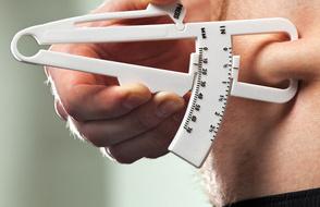 Körperfettanteil berechnen: Foto von einer Körperfettmessung mit einem Caliper oder Körperfettzange.