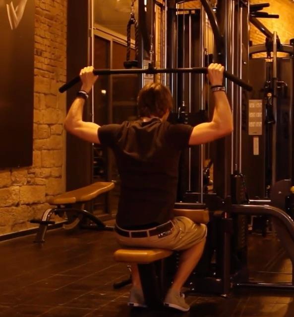 Muskelaufbau Tipps: Foto von einem Mann bei der Fitness-Übung Lat-Zug für den oberen Rücken.