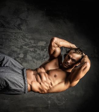 Bauchmuskeln trainieren: Foto von einem muskulösen Mann beim Bauchtraining mit freiem Oberkörper.