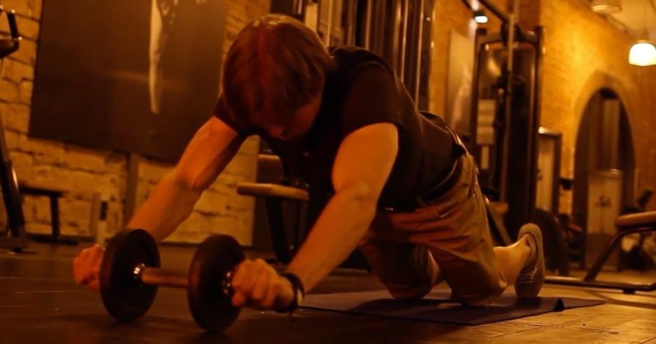 Effektives Bauchtraining: Foto von einem muskulösen Mann beim Bauchtraining mit einer Kurzhantel.