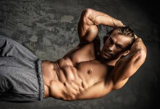 Effektives Bauchtraining: Foto von einem muskulösen Mann beim Bauchtraining mit freiem Oberkörper.
