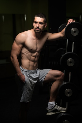 Ektomorph : Foto von einem muskulösen Mann mit Waschbrettbauch im Fitnessraum.
