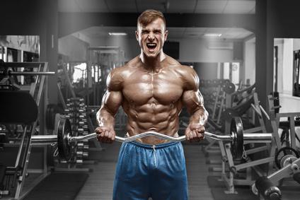 Ernährungsplan Muskelaufbau: Foto von einem muskulösen Mann mit Waschbrettbauch und Langhantel im Fitnessstudio.