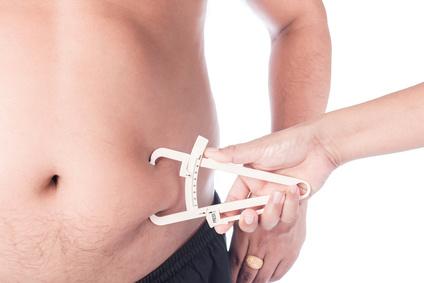 Körperfettanteil: Foto von einer Körperfettmessung von einem dicken Männer Bauch mit einem Caliper oder Körperfettzange.