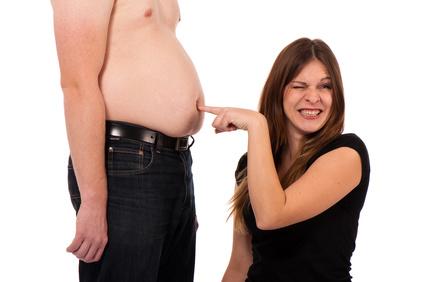 Bauchspeck loswerden: Foto von einem dicken Bauch auf den eine Frau tippt