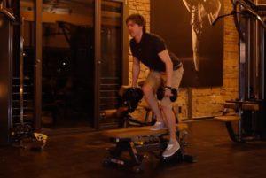 Beinbeuge: Foto von einem Mann bei Übung einbeiniger Beinbeuger auf einer Bank