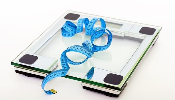 Körperfettanteil berechnen: Foto von einer Waage mit einem Maßband oben auf liegend