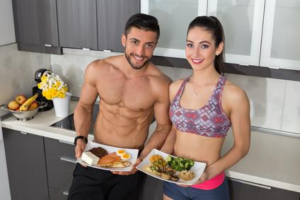 täglicher Kalorienbedarf: Foto von trainiertem Mann und Frau mit Essen in der Küche