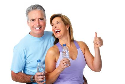 Körperfettanteil: Foto von einem lachenden älteren Ehepaar Wasser in der Hand