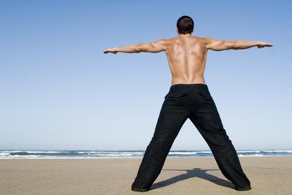Rückenmuskulatur aufbauen: Foto von einem durchtrainierten Mann von hinten am Strand
