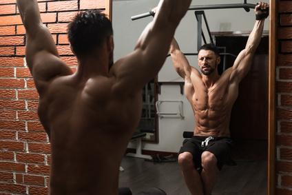 untere Bauchmuskeln trainieren: Foto von einem Mann bei Bauchübungen an der Klimmzugstange