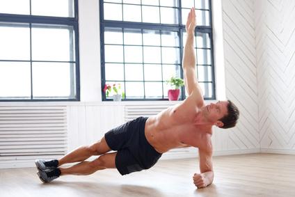 Bauchtraining Mann zu Hause: Foto von einem Mann bei der Bauch-Übung seitlicher Unterarmstütz.