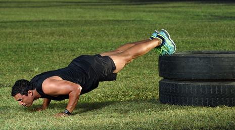 Brustmuskeln trainieren: Foto von einem Mann bei der Brust-Übung Liegestützen mit Erhöhung der Beine.