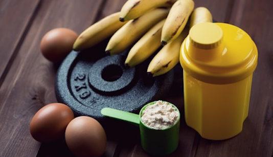 Ernährungsplan Muskelaufbau Mann: Foto von einer Hantelscheibe, Bananen, Eier, Eiweißpulver und einem Eiweißshake.