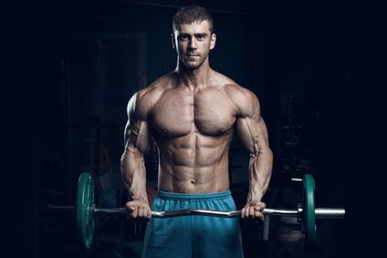 Ernährungsplan Muskelaufbau Mann: Foto von einem Mann mit viel Muskeln beim Krafttraining mit Langhantel.