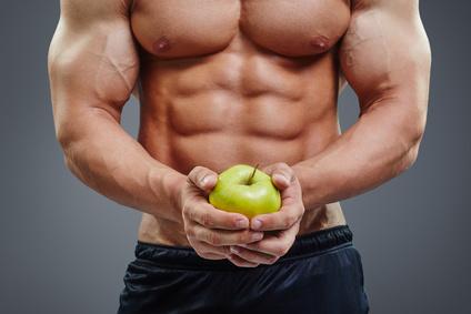 Ernährungsplan Muskelaufbau Mann: Foto von einem Mann mit viel Muskeln und einem Apfel in der Hand.