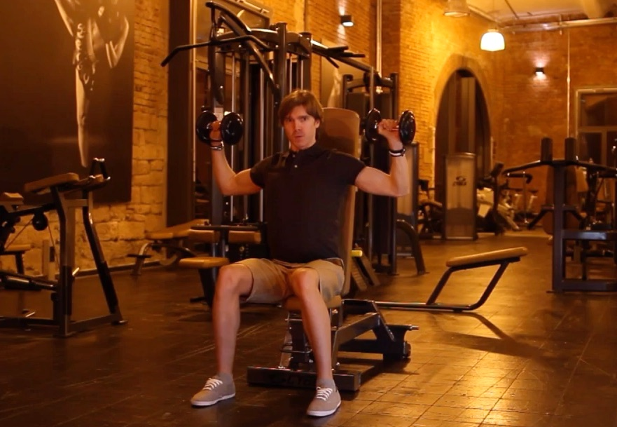Krafttraining mit Kurzhanteln: Foto von einem Mann Bei der Schulter-Übung Schulterdrücken.