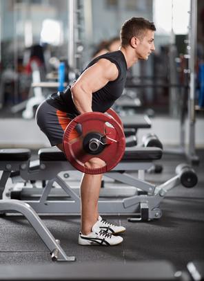 Kurzhantelrudern: Foto von einem Mann bei der Rücken-Übung Bankziehen mit Langhantel.