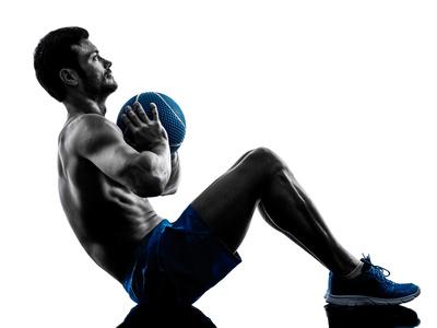 Rumpfbeugen: Foto von einem Mann beim Bauchtraining auf dem Boden mit einem Medizinball.