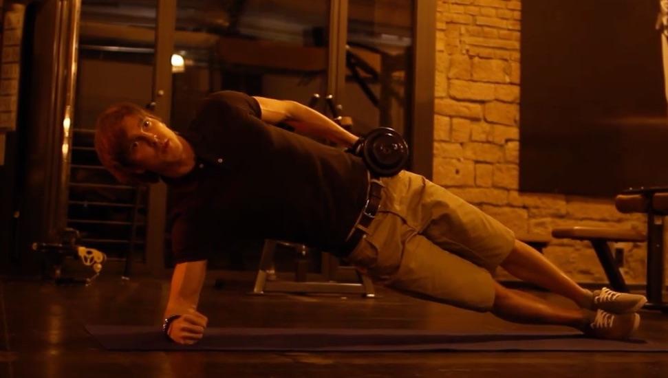 Rumpfbeugen: Foto von einem Mann bei einer Bauchübung mit Kurzhantel.