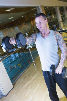 Schulterübungen: Foto von einem Mann beim Frontheben mit Kurzhanteln.