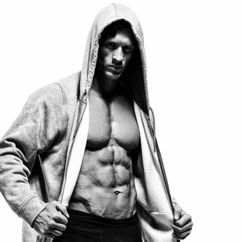 Sixpack antrainieren : Foto von einem muskulösen Mann mit Waschbrettbauch und einem Kapuzen-Pullover an.