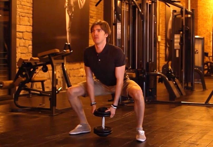 Adduktoren Training: Foto von einem Mann beim Adduktoren-Training zuhause mit Kurzhantel.
