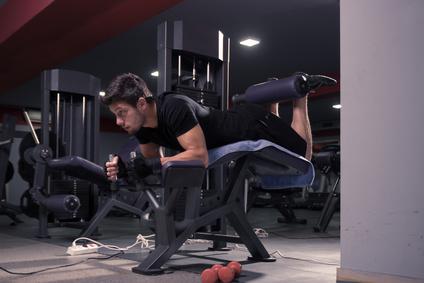 Foto von einem Mann bei der Bein-Übung an der Beinbeuger Maschine liegend.