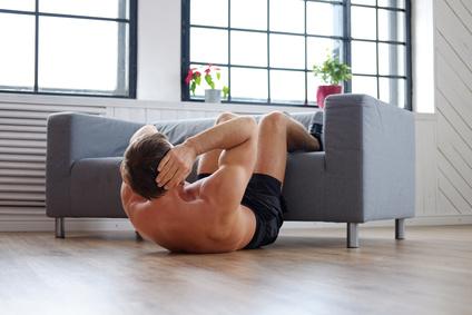 Effektives Bauchmuskeltraining: Foto von einem Mann bei der Bauch-Übung Situps mit den Waden auf der Couch.