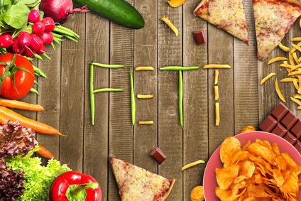 Ernährungsplan Fettabbau: Foto von gesundem Gemüse auf der linken Hälfte und ungesundem Essen wie Pizza, Chips und Pommes rechts. Slogan Fit oder Fett.