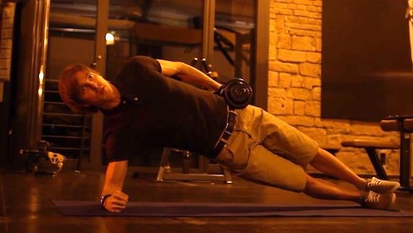 Ganzkörpertraining Übungen: Foto von einem Mann bei der Bauch-Übung seitliches Hüftheben mit Kurzhantel.