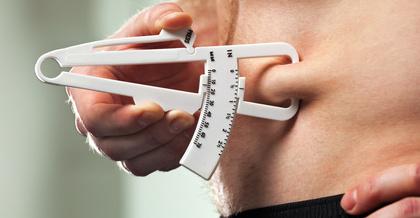 Körperfettanteil Sixpack: Foto von einem Mann mit Bauchfett und einer Fett-Zange zum Körperfettanteil messen.