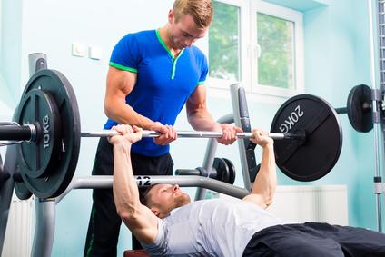Foto von einem Mann beim Langhanteltraining mit der Übung Bankdrücken Langhantel mit einem Trainingspartner.