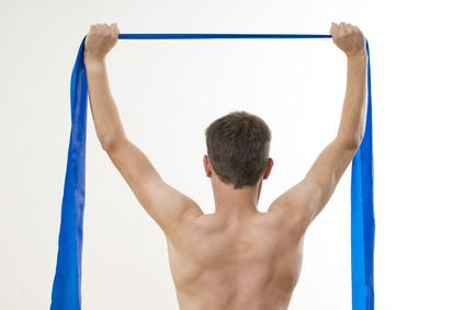 Lat ziehen: Foto von der Ansicht des oberen Rückens eines Mannes mit einem Theraband in der Hand.