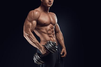 Muskelaufbau und Fettabbau: Foto von einem muskulösen Mann mit einer schweren Kurzhantel in der rechten Hand.