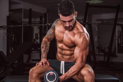 Oberarmtraining: Foto von einem muskulösen Mann bei der Bizeps-Übung Kurzhantelcurls.