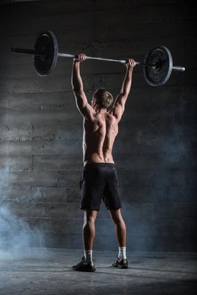 Schulterdrücken Kurzhantel: Foto von einem Mann bei der Schulterübung Schulterdrücken mit Langhantel.