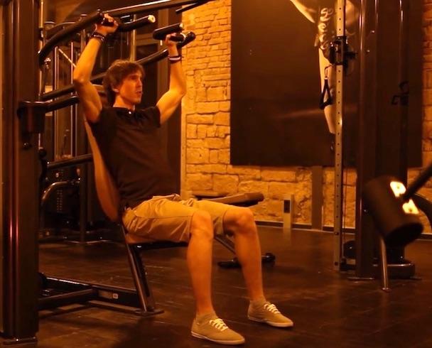 Schulterdrücken Kurzhantel: Foto von einem Mann bei der Schulterübung Schulterdrücken an der Maschine.