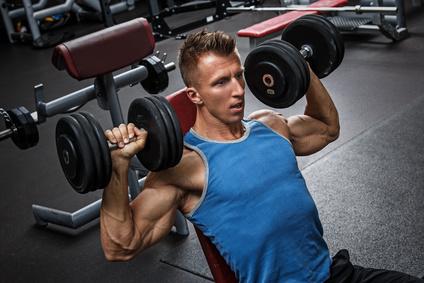Schulterdrücken Kurzhantel: Foto von einem Mann bei der Schulterübung Schulterdrücken mit Kurzhanteln.