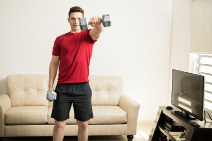 Schultertraining Kurzhantel: Foto von einem Mann bei der Schulter-Übung Frontheben Kurzhantel.