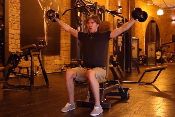 Schultertraining Kurzhantel: Foto von einem Mann bei der Schulter-Übung Seitheben Kurzhantel sitzend.