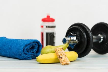 Sixpackernährung: Foto von einer Hantel und kohlenhydratreichen Lebensmitteln wie Müsliriegel, Birne und Banane.