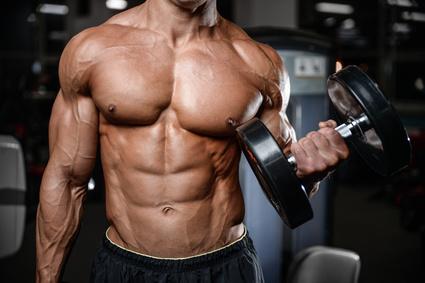 Testosteronmangel was tun: Foto von einem sehr muskulösen Mann mit einer schweren Kurzhantel in der Hand.