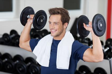 Foto von einem Mann bei der Schulter-Übung Überkopfdrücken mit Kurzhanteln.