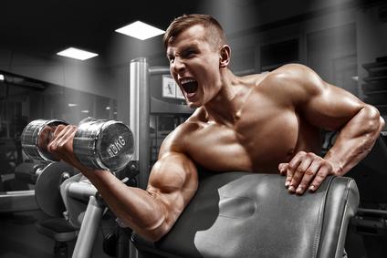 Wie dicke Oberarme bekommen? Foto von einem muskulösen Mann mit bei der Bizeps-Übung Scottcurls.