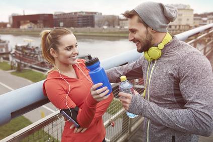 Wie kann ich mich zum Krafttraining motivieren? Foto von einer Frau und einem Mann als Freunde beim Spaß durch Musik beim Sport.