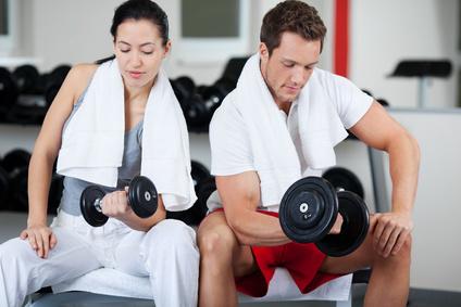 Wie motiviere ich mich zum Sport? Foto von einer Frau und einem Mann als Trainingspartner beim Hanteltraining.